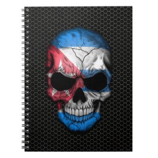 Cráneo cubano de la bandera en el gráfico de acero cuaderno