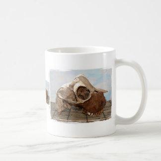Cráneo de la cabra en mate de bambú contra la part tazas de café