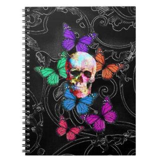 Cráneo de la fantasía y mariposas coloreadas libreta espiral