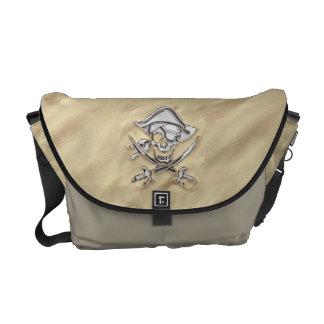 Cráneo de plata del pirata en la arena bolsa de mensajeria