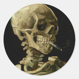 Cráneo de un esqueleto con el cigarrillo ardiente pegatina redonda