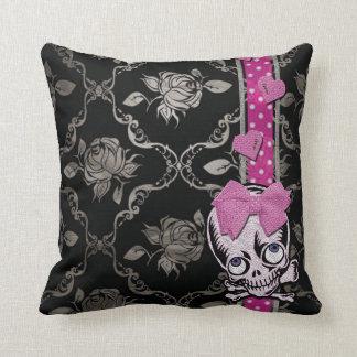 Cráneo espeluznante del chica con el arco rosado e almohadas
