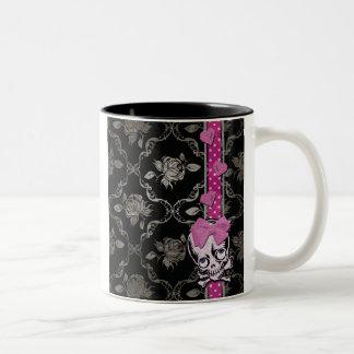 Cráneo espeluznante del chica con el arco rosado e tazas de café
