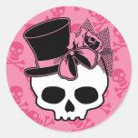 Cráneo femenino con el gorra y el arco rosado etiqueta redonda