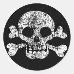 Cráneo gastado y bandera pirata etiqueta redonda