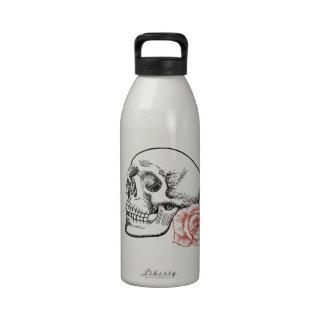 Cráneo humano con el dibujo lineal del rosa rojo botellas de beber