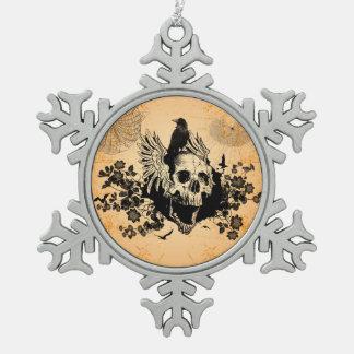 Cráneo impresionante con las alas y el cuervo adorno de peltre en forma de copo de nieve