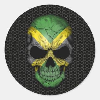 Cráneo jamaicano de la bandera en el gráfico de pegatina redonda