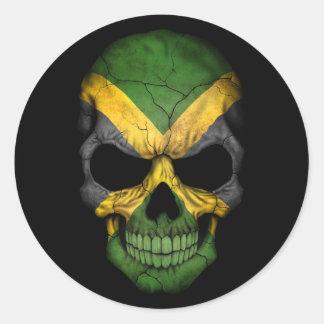 Cráneo jamaicano de la bandera en negro etiqueta redonda