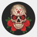 Cráneo oscuro del azúcar con los rosas rojos pegatinas redondas
