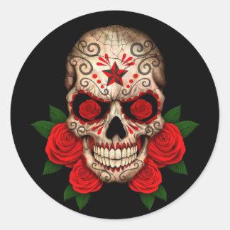 Cráneo oscuro del azúcar con los rosas rojos pegatina redonda