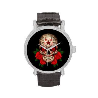 Cráneo oscuro del azúcar con los rosas rojos relojes