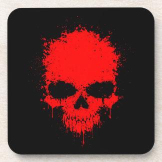 Cráneo rojo de la salpicadura del goteo posavaso