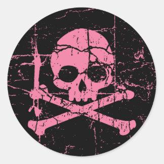 Cráneo rosado gastado y bandera pirata pegatina redonda