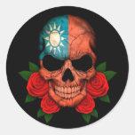 Cráneo taiwanés de la bandera con los rosas rojos pegatina redonda