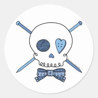 Cráneo y agujas que hacen punto (azules) pegatina redonda