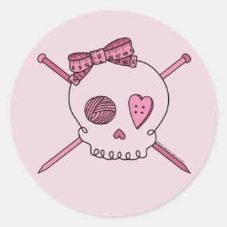 Cráneo y agujas que hacen punto (fondo rosado) pegatina redonda