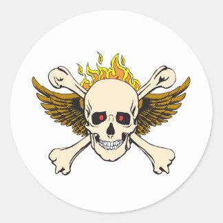 Cráneo y alas con bandera pirata y fuego pegatina redonda