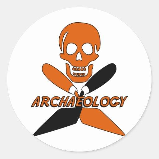 Cráneo y arqueología cruzada de las paletas etiqueta redonda