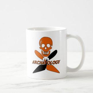 Cráneo y arqueología cruzada de las paletas taza de café
