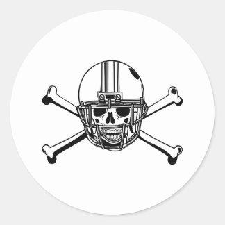 Cráneo y futbolista de los huesos de la cruz etiqueta redonda