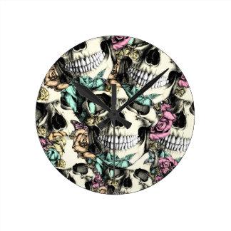 Cráneos color de rosa descendentes con las maripos reloj redondo mediano