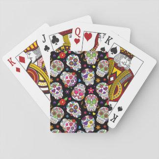 Cráneos coloridos del azúcar en negro baraja de cartas
