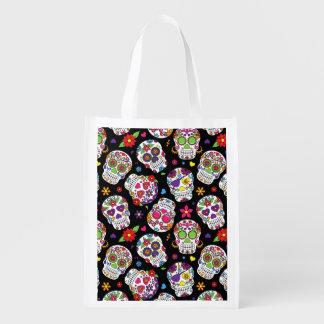 Cráneos coloridos del azúcar en negro bolsas de la compra
