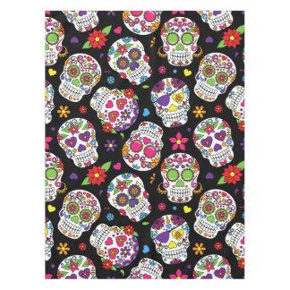 Cráneos coloridos del azúcar en negro mantel de tela