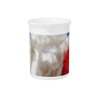 Cream with strawberries in a glass bowl drink pitcher