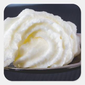crema en un concepto de la macro de la cuchara pegatina cuadrada