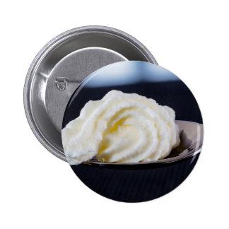 crema en un concepto de la macro de la cuchara pin redondo de 2 pulgadas