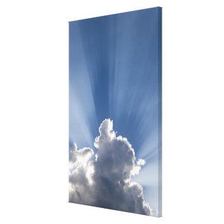 Crepuscular or God's rays streak past cloud. Canvas Print