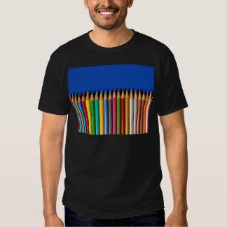 Creyones coloridos del lápiz en fondo azul playeras