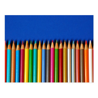 Creyones coloridos del lápiz en fondo azul postal