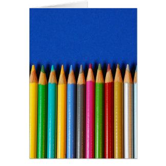 Creyones coloridos del lápiz en fondo azul tarjeta de felicitación