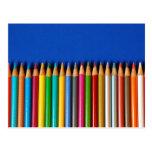 Creyones coloridos del lápiz en fondo azul tarjetas postales