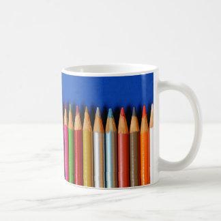 Creyones coloridos del lápiz en fondo azul taza clásica