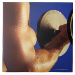 Cropped shot of man lifting weights tile