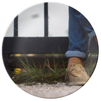 Crossed feet in front of iron fence porcelain plate