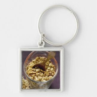 Crunchy muesli with wooden spoon in a measuring keychain