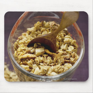 Crunchy muesli with wooden spoon in a measuring mouse pad
