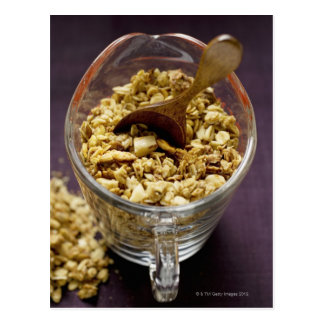 Crunchy muesli with wooden spoon in a measuring postcard