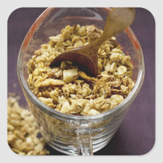 Crunchy muesli with wooden spoon in a measuring square sticker