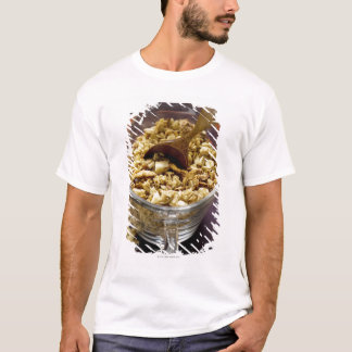 Crunchy muesli with wooden spoon in a measuring T-Shirt