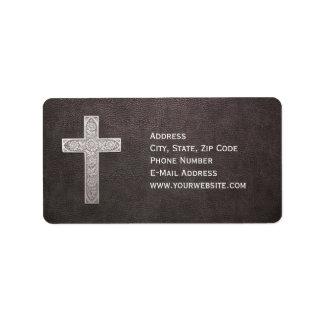 Cruz del metal en el cuero oscuro etiqueta de dirección