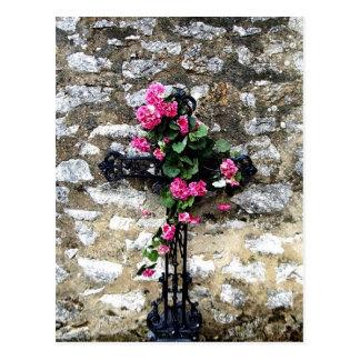Cruz dulce gótica del cementerio con las flores postal
