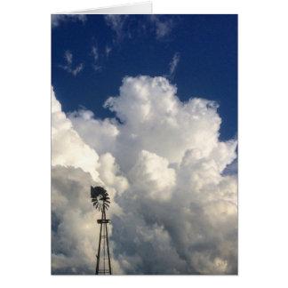 Cruz en la tarjeta de nota en blanco de las nubes