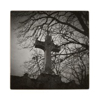 Cruz grave del cementerio abrigada por las ramas posavasos de madera