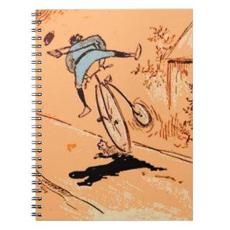 Cuaderno chistoso del naranja del gato de la bicic